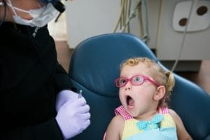 Little girl with mouth open for dental check up