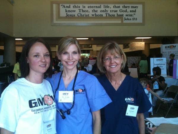 Photo of three Cheek Dental team members, including Dr. Cristi Cheek, volunteering at the Georgia Mission of Mercy.