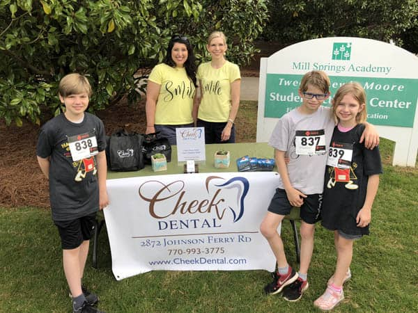 Outdoors photo of Dr. Kristi Chandler and Dr. Crisit Cheek behind a display table at the for the Nacho Ordinary 5k. Dr. Cheek's three children are in the forefront of the photo on either side of the table.